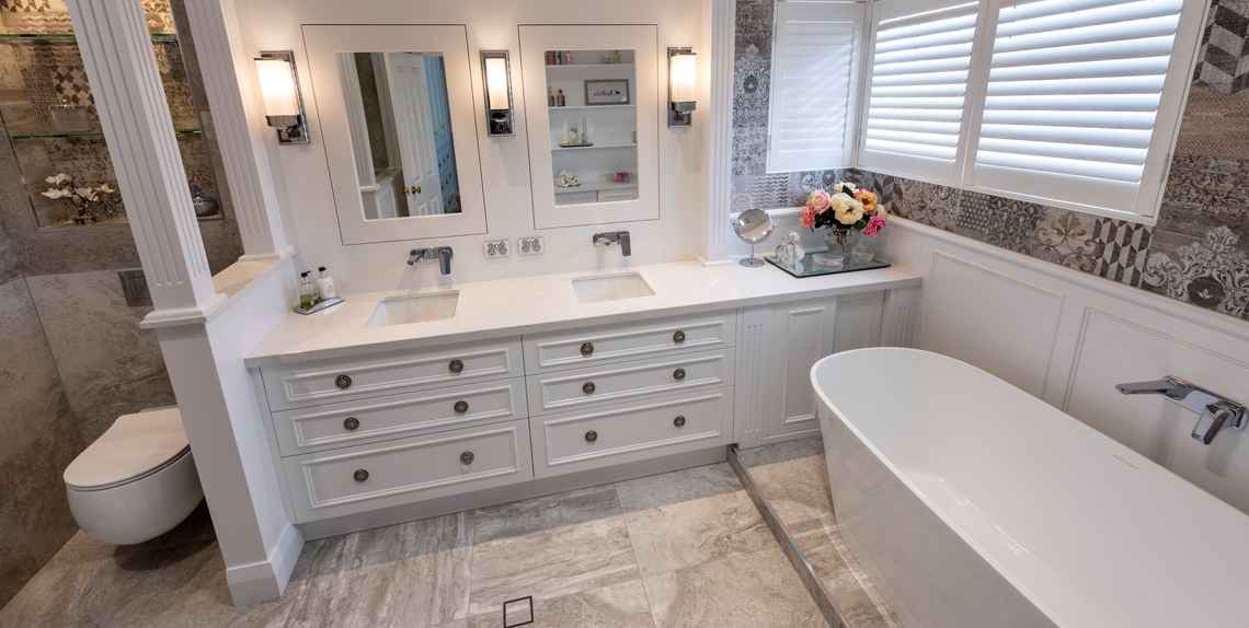 White double bathroom sinks against a grey tile finish bathroom.