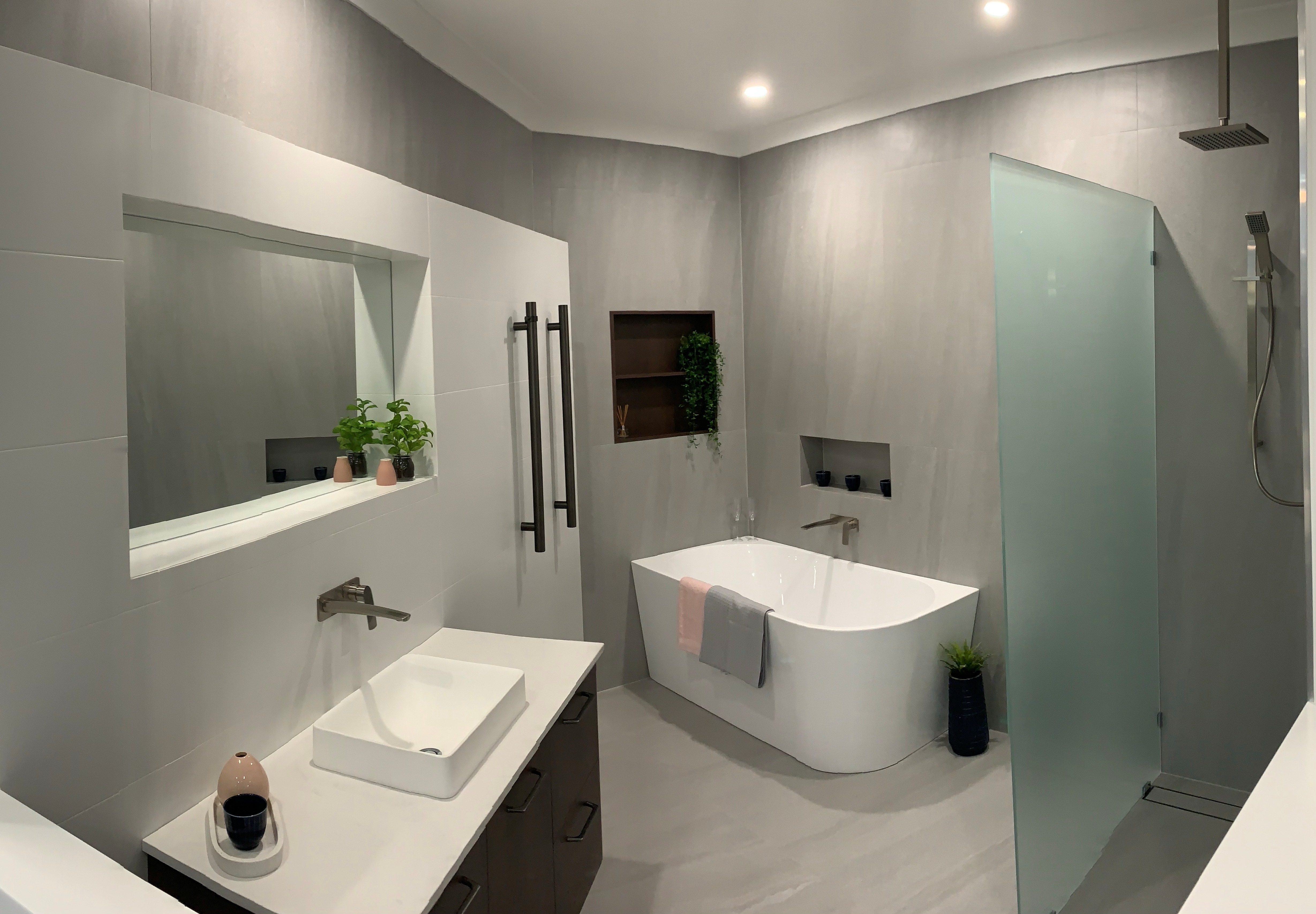Large open plan bathroom with light brown cabinets.