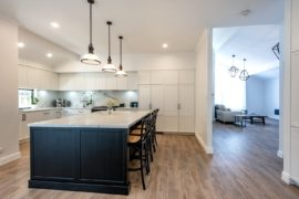 modern luxurious open plan kitchen with marble top island downlights and light wooden floors leading into loving room